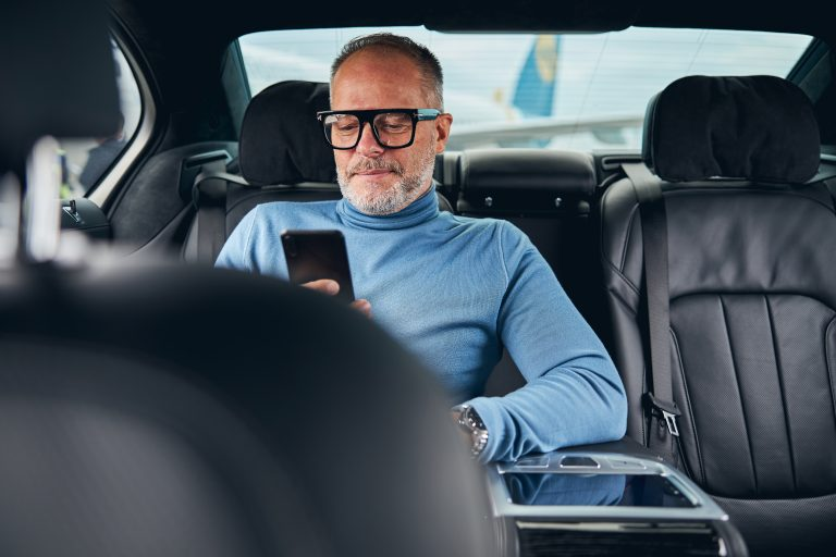 Front view of a smiling businessman reading news on his cellular phone in the cab