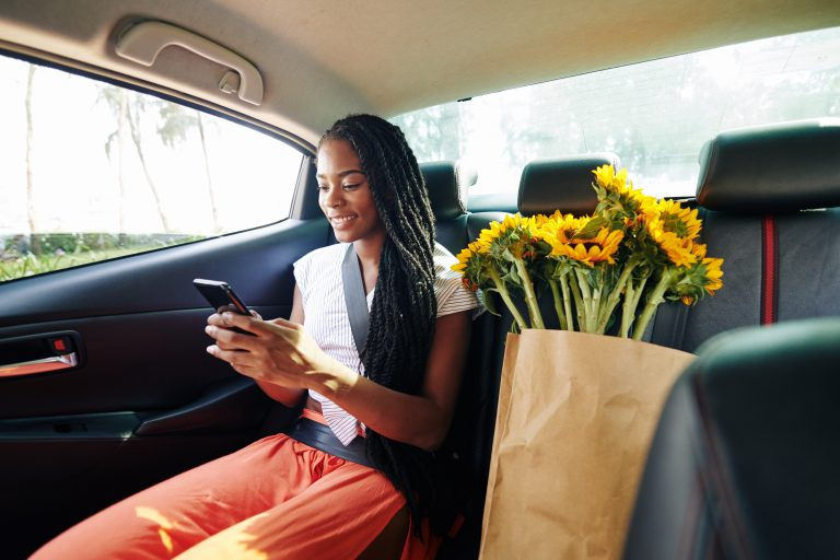 Beautiful positive young Black woman riding in taxi after supermarket and reading text messages from friends